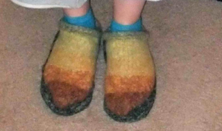 Clogs, felted, on the feet of the recipient.