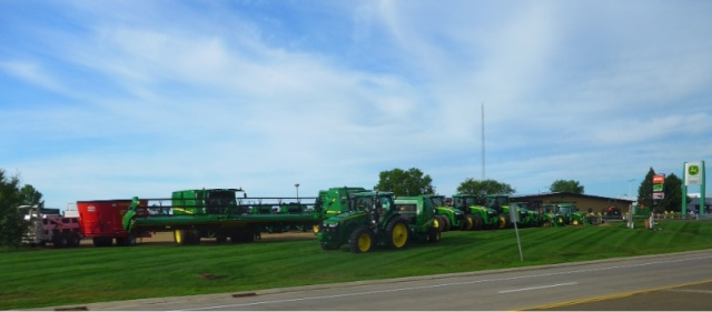 Tractors, etc. on outdoor display at an implement dealer.